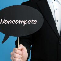 Noncompete. Businessman (Man) is holding the sign of speech bubble in his hand. Handwritten Text on the Label. Business, Finance, Analysis, Economy